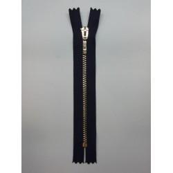 Cremallera negra de 25 cms con malla de color oro claro visible. Ideal para dar un toque original a tus prendas y complementos.