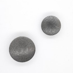 Botón metálico negro pavonado de rayas decorativas.