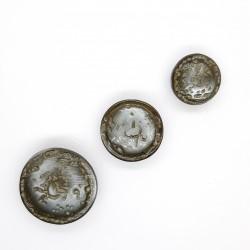 Botón metálico de color plata vieja verdosa.