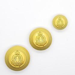 Botón dorado metálico con escudo decorativo.